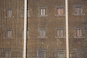 Large metal internal security fence that surrounds a Prison Wing of HMP Pentonville, London, UK.  The windows of individual cells can be seen through the fence. (Photo by Andy Aitchison)