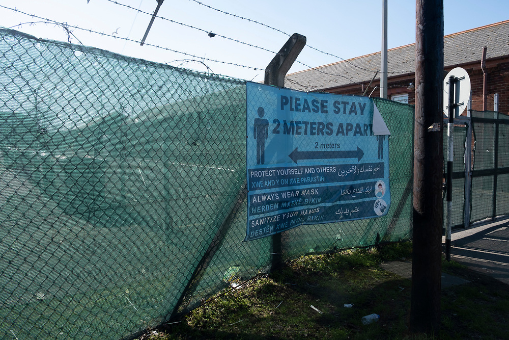 A safety sign at in English, American, Kurdish and Arabic to protect people against the spread of COVID-19 at the entrance to Napier Barracks on the 9th of March 2021 in Folkestone, United Kingdom. The sign asks people to stay 2 meters apart, protect yourself and others, always wear a mask and sanitise your hands. Over 400 asylum seekers are being kept at Napier Barracks in unsuitable, cold accommodation, they are experiencing mental health issues as well as being vulnerable to health conditions including COVID-19. In January 2021 over 200 people inside the centre tested positive for COVID-19. (photo by Andrew Aitchison / In pictures via Getty Images)