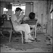 A vietnamese barber is joking with a customer while he's cleaning his hear. Danang, Vietnam, Asia