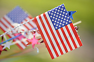Merrick, New York, U.S. - May 26, 2014 - American flags and red white and blue decorations, seen close up, decorating a memorial wreath at The Merrick Memorial Day Parade and Ceremony, hosted by American Legion Post 1282 of Merrick, honoring those who died in war while serving in the United States military.