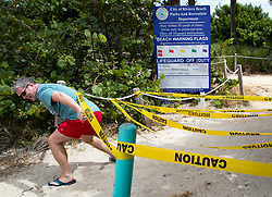 October 2, 2018 - Riviera Beach, Florida, U.S. - DAVID BEYGA, visiting from the UK, slips under the caution tape after taking a look at the beach on Singer Island. Beaches were shut down in Palm Beach County following complaints of respiratory, skin and eye irritations. (Credit Image: © Allen Eyestone/The Palm Beach Post via ZUMA Wire)