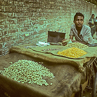 A boy sells nuts to passersby on a street in  Dhaka, Bangladesh.