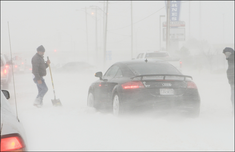 Drivers dig their cars out of the snow during a Blizzards in Oklahoma City, OK.