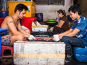 "11 JUNE 2015 - MAHACHAI, SAMUT SAKHON, THAILAND: Burmese migrant workers at the Samut Sakhon shrimp market in Mahachai clean squid. Labor activists say there are about 200,000 migrant workers from Myanmar (Burma) employed in the fishing and seafood industry in Mahachai, a fishing port about an hour southwest of Bangkok. Since 2014, Thailand has been a Tier 3 country on the US Department of State Trafficking in Persons Report (TIPS). Tier 3 is the worst ranking, being a Tier 3 country on the list can lead to sanctions. Tier 3 countries are ""Countries whose governments do not fully comply with the minimum standards and are not making significant efforts to do so."" After being placed on the Tier 3 list, the Thai government cracked down on human trafficking and has taken steps to improve its ranking on the list. The 2015 TIPS report should be released in about two weeks. Thailand is hoping that its efforts will get it removed from Tier 3 status and promoted to Tier 2 status.        PHOTO BY JACK KURTZ"