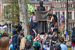 © Licensed to London News Pictures. 18/04/2019. London, UK. Protesters arriving from Scotland clamber over a statue of suffragist leader Millicent Fawcett in Parliament Square, as protestors from Extinction Rebellion occupy the area for a fourth day. Protesters are demanding urgent government action on climate change. Photo credit: Ben Cawthra/LNP