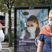 People wait for a tram in front of a poster raising awareness to wearing a mask is required as part of the COVID-19 preventive regulations in Budapest, Hungary on Sept. 23, 2020. ATTILA VOLGYI