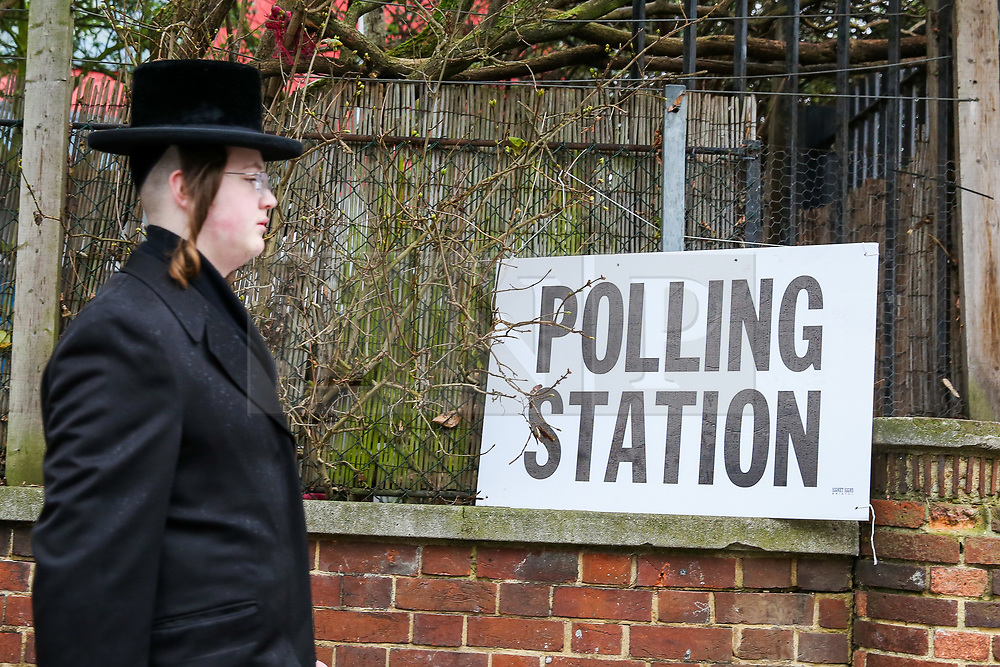 © Licensed to London News Pictures. 12/12/2019. London, UK. An Orthodox Jewish man walks past a polling station sign in Stamford Hill, north London. Voters are voting today, as the nation decides the next UK Government in the first December General Election since 1923.  Photo credit: Dinendra Haria/LNP