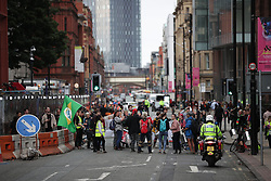 © Licensed to London News Pictures. 30/08/2019. Manchester, UK. Extinction Rebellion block a block of roads around Deansgate during the rush hour , in Manchester City Centre , at the start of several days of planned disruption organised by environmental campaigners . Manchester City Council has declared a climate emergency but activists say the council's development plans do not reflect this . Photo credit: Joel Goodman/LNP