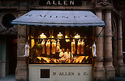 A portrait of two butchers standing in the window of R Allen & Co, Mayfair, London, the oldest and finest butchers in the capital. It is dawn one morning and joints of lamb and pork hang from hooks in the window while rabbits are on the canopy rail outside the shop at 117, Mount Street and built in 1887.