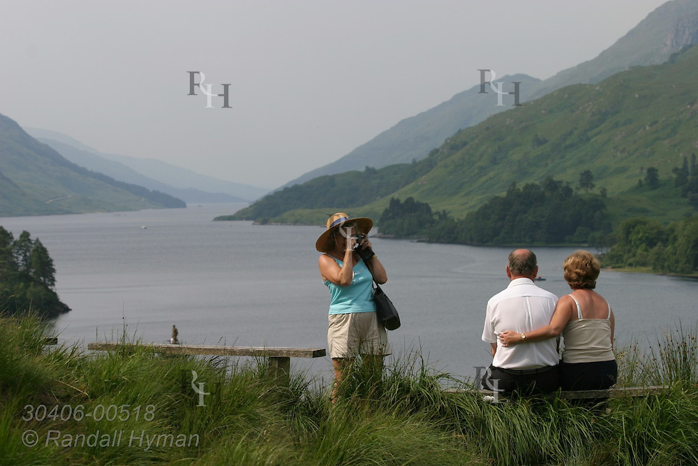Woman photographs couple on bench overlooking Loch Shiel; Glenfinnan, Scotland.