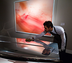 London, September 29 2017. A gallery assistant polishes Marc Newson's Event Horizon Table, estimated at between £100,000 - 150,000), with  Wolfgang Tillman's Urgency XVI, estimated to fetch between £300,000 - 500,000 in the background at Christie's Masterpieces of Design and Photography sale in London on 3rd October 2017. © Paul Davey