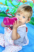 14 month old baby girl with blond hair, drinks from a bottle. Model Release Available