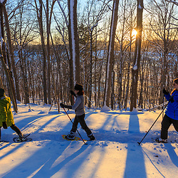 Three women snowshoeing while the sun shines through the forest above Indian Hill Reservoir in West Newbury, Massachusetts.