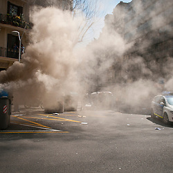 Traffic police arrive as smoke billows out of a garbage container.