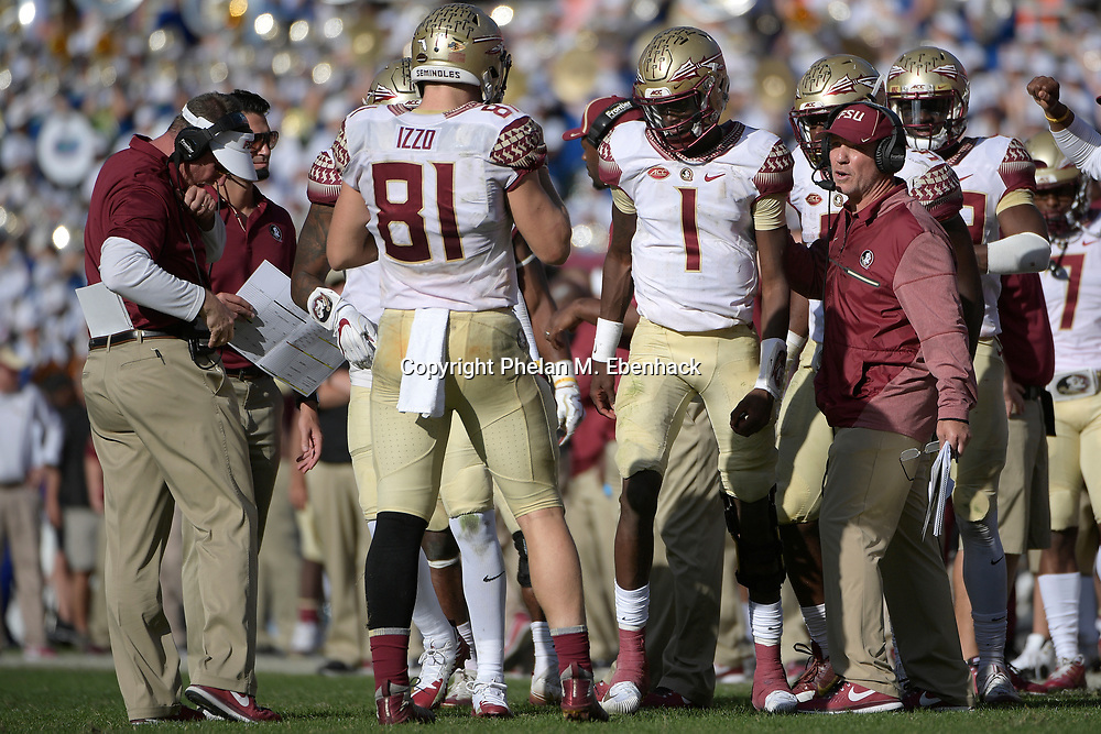 Florida State head coach Jimbo Fisher, right, gives instructions to quarterback James Blackman (1) during the second half of an NCAA college football game against Florida Saturday, Nov. 25, 2017, in Gainesville, Fla. FSU won 38-22. (Photo by Phelan M. Ebenhack)