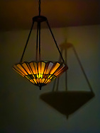 stained glass ceiling lamp and its shadow on the wall
