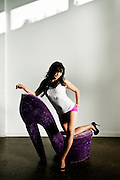 Boudoir Portraiture of woman in heels and pink panties leaning against oversized purple velvet shoe