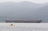 New Windsor, New York - A man paddles his kayak on the Hudson River as the tanker barge RTC 120 heads south in the background at the Paddlefest event sponsored by the Mid-Hudson Chapter of the Adirondack Mountain Club at Kowawese Unique Area at Plum Point June 13, 2010. The barge is 405 feet long.