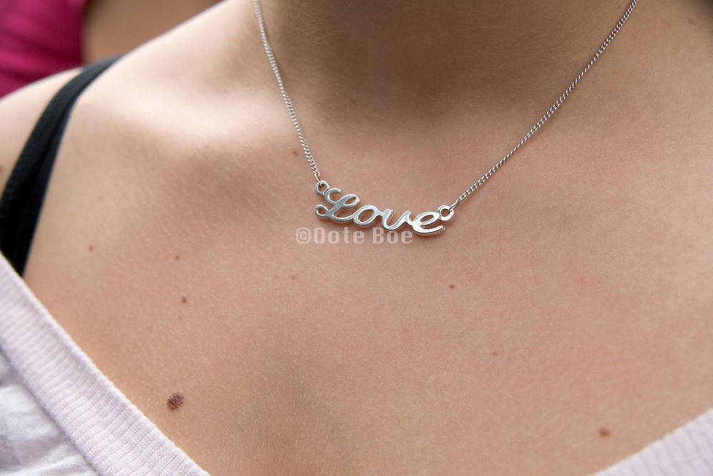 young girl with a silver necklace with the text love