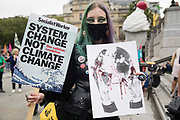 An activist holds two placards in Trafalgar Square on the first day of Extinction Rebellions Impossible Rebellion protests on 23rd August 2021 in London, United Kingdom. Extinction Rebellion are calling on the UK government to cease all new fossil fuel investment with immediate effect.
