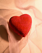 Close up, colorful photo of a sculpture of a red heart sitting in gauze cloth