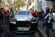Protesters pass a Rolls Royce car for the Global Climate Strike organised by UK Student Climate Network on 29th November 2019 in London, United Kingdom. The School strike for climate, also known as Fridays for Future, FFF, Youth for Climate and Youth Strike 4 Climate, is an international movement of school students who are deciding not to attend classes and instead take part in demonstrations to demand action to prevent further global warming and climate change. UK Student Climate Network is calling on everyone - adults, workers, community groups, trade unionists, nurses, teachers, steel workers, car manufacturers, waiters and everyone else in between to join them in a global general climate strike. This protest will join people all around the world in a massive day of climate action.