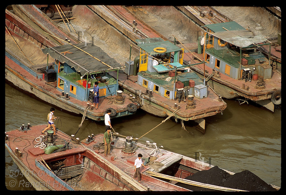 Men tie barges beside one another on Huangpu River in this view from tallest bridge in Shanghai. China
