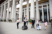 Man policing the public on a Segway two wheeled vehicle outside The National Museum of China. Flanking the eastern side of Tiananmen Square in Beijing, China. The mission of the museum is to educate about the arts and history of China. It is directed by the Ministry of Culture of the People's Republic of China. The museum was established in 2003 by the merging of the two separate museums that had occupied the same building since 1959. The building was completed in 1959 as one of the Ten Great Buildings celebrating the ten-year anniversary of the founding of the People's Republic of China. After four years of renovation, the museum reopened on March 2011 with 28 new exhibition halls, more than triple the previous exhibition space, and state of the art exhibition and storage facilities. It has a total floor space of nearly 200,000 square meters to display. The renovations were designed by the German firm Gerkan, Marg and Partners.