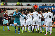 Swansea city players surround referee Anthony Taylor to appeal and Lukasz Fabianski complains after Sam Vokes of Burnley handles the ball but the referee Anthony Taylor thinks it was a Swansea city players arm and awards a penalty to Burnley by mistake. Burnley's Andre Gray goes on to score the penalty. Premier league match, Swansea city v Burnley at the Liberty Stadium in Swansea, South Wales on Saturday 4th March 2017.<br /> pic by Andrew Orchard, Andrew Orchard sports photography.