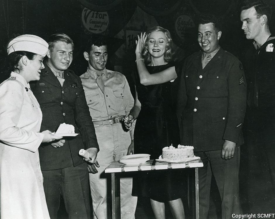 1944 Actress Gloria Grahame cuts a birthday cake at the Hollywood Canteen.