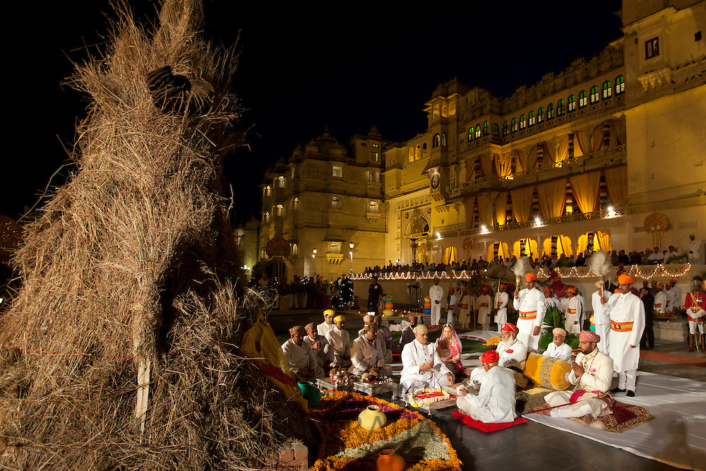 Shriji Arvind Singh Mewar of Udaipur, 76th Custodian of the House of Mewar, presides at annual Hindu Holi Fire Festival at The Zenana Mahal in the City Palace, Udaipur, Rajasthan, India. On his left is son  and heir Lakshyaraj Singh Mewar of Udaipur, Maharaj Kumar and on right Maharani Vijaya Laxmi. Hindu priests conduct Puja worship ceremony...