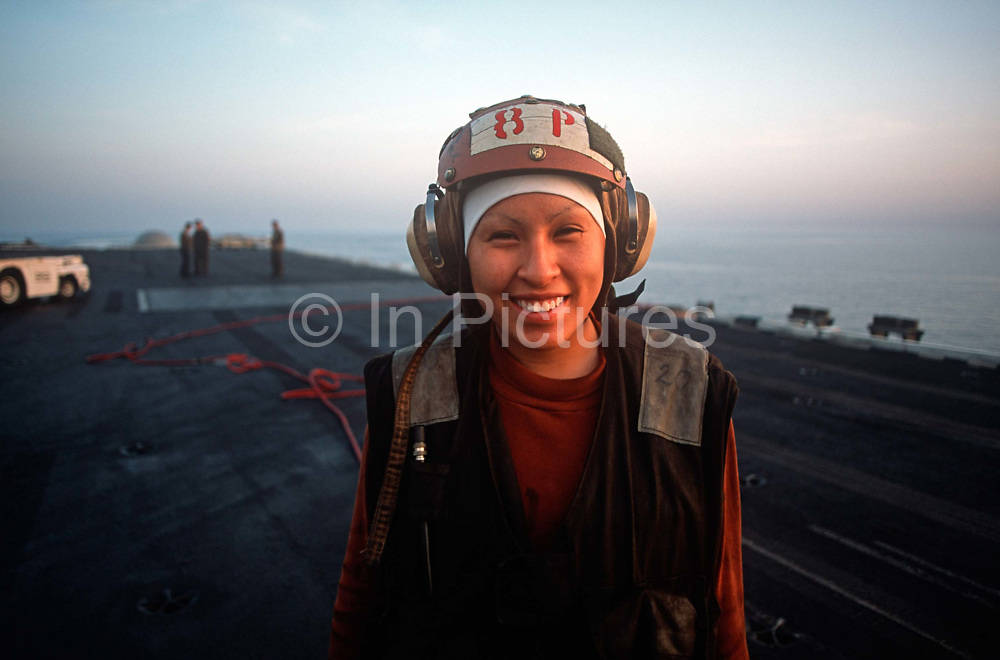 Portrait of a female US Navy crew member on the deck of US Navy aircraft carrier USS Harry S Truman during its deployment patrol of the no-fly zone at an unknown location in the Persian Gulf, on 8th May 2000, in the Persian Gulf. The Truman is the largest and newest of the US Navys fleet of new generation carriers, a 97,000 ton floating city with a crew of 5,137, 650 are women.
