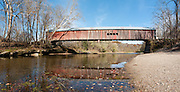 Cox Ford Covered Bridge was built in 1913 in Burr Arch style by J.A. Britton over Sugar Creek. A roof and red painted wood sides protect this historic bridge in Turkey Run State Park, in historic Parke County, Indiana, USA. Panorama stitched from 6 photos.