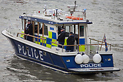 Metropolitan (Met) Police officers seen on their River Thames high-speed emergency patrol boat attending to the flotilla of assorted boats celebrating the Queen's record of years as monarch. On the river opposite the Houses of Parliament in Westminster, the officers oversee the safety of those participating the ceremonial event. Seen from the rear, we see the boat's fenders and emergency equipment on the roof. The men and woman wear life vests too.
