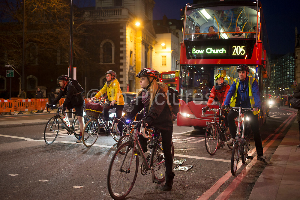 Cyclists waiting at traffic lights on Bishopsgate in the City of London. Cycling has become a very popular mode of transport in the capital as people try to avoid public transport, saving money, getting fit and saving time.