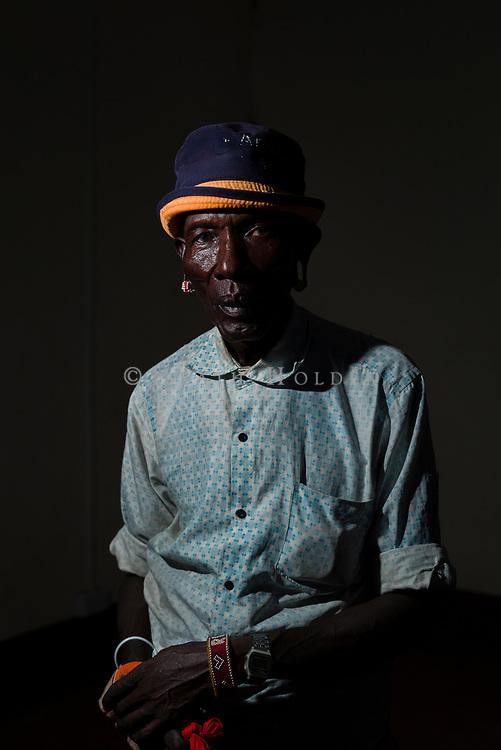A Samburu elder stands for a portrait in a dimly lit room.