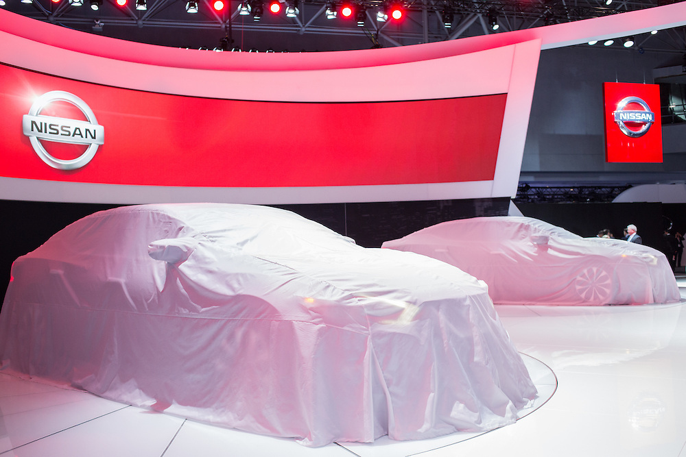 New York, NY - 1 April 2015. Two Nissan Maximas wait under veils at the New York International Auto Show, their lights visible through the covers.