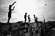 By late afternoon in Navotas cemetery youth launch their kites in the wind enjoying the evening breeze at the very top of the graves.