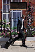 A businessman pulls his case past the construction hoarding belonging to Claridges in Mayfair, Westminster.