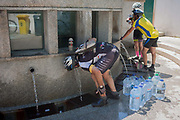 Cyclists drink thermal spring water at Fonte de Sao Joao, on 17th July 2016, in the spa resort of Luso, Portugal. In the 11th century, Luso was a sleepy village linked to a monastery in the hills near Coimbra but it became a lively spa resort in the 1700s as its hot water springs became a focus for tourism. The waters here are said to have therapeutic value in the treatment for bad circulation, muscle tone, rheumatism and renal problems.