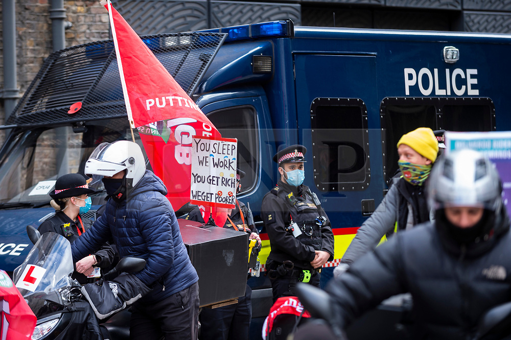 © Licensed to London News Pictures. 07/04/2021. LONDON, UK.  Police look on as Deliveroo riders and drivers on strike stage a protest outside the company's headquarters in Cannon Street against the company demanding improvements to pay and conditions in terms of minimum wage, holidays and sick leave.  The strike comes on the same day that the company's shares are publicly traded for the first time following its initial public offering (IPO) on 31 March, where shares fell by 25% after failing to receive support by institutional investors who cited concerns about the company's policy on workers' rights.  Photo credit: Stephen Chung/LNP