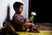 Faizan, 14, is sitting inside his home in Arif Nagar, one of the water-affected colonies standing next to the abandoned Union Carbide (now DOW Chemical) industrial complex in Bhopal, Madhya Pradesh, central India. Since this image was taken, Faizan has deceased.