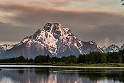 Mount Moran and the Grand Teton mountains reflected on the Snake River at Oxbow Bend at dawn with the rising sun reflected on clouds at the Grand Teton National Park in Moran, Wyoming.