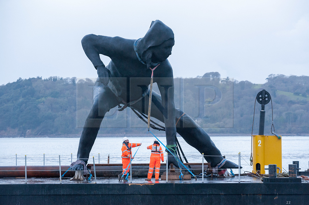 """© Licensed to London News Pictures. 18/03/2019. Plymouth, Devon, UK. """"Messenger"""", the largest bronze sculpture ever to be cast in the UK, is transported by barge across Plymouth Sound before being installed at the Theatre Royal in Plymouth City Centre. Weighing in at nine and a half tonnes with a height of seven metres (23ft) and nine metres (30ft) wide, with a volume of 25.6 metres cubed, """"Messenger"""" will be the size of two double decker buses and is the largest lost-wax cast bronze sculpture ever to be cast in the UK, a painstaking process that has taken over two years. """"Messenger"""" is the work of the acclaimed sculptor Joseph Hillier and has been created using 3D scans from the body of a young actor in mid-performance in Theatre Royal Plymouth and Frantic Assembly's production of Othello in 2014. A monument to the physical expression of theatre, """"Messenger"""" is a movement suspended in time that embodies the energy and creativity at the heart of the Theatre Royal and cultural life in Plymouth and aims to celebrate creativity as a dynamic catalyst for change. Plymouth is undergoing massive regeneration and the installation of the sculpture is is a prelude to the Mayflower 2020 celebrations. Messenger was cast at the Castle Fine Arts Foundry in the Welsh village of Llanrhaeadr-Ym-Mochnant, using the ancient technique of lost wax casting. Made from over 200 bronze panels, each section of the sculpture was cast individually before being welded together by over 30 master craftsmen at the foundry. Photo credit: Simon Chapman/LNP"""