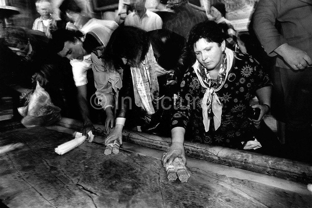 Pilgrims revere the Stone of Unction upon which Jesus was annointed before his burial Holy Sepulchre, Jerusalem, Israel