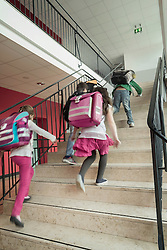 Rear view of school students running up stairs, Bavaria, Germany