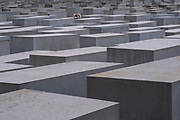 A woman taking a picture inside the Holocaust memorial, a memorial in Berlin, Germany to the Jewish victims of the Holocaust designed by architect Peter Eisenman and engineer Buro Happold. It consists of 2,711 concrete slabs  covering a 19,000-square-metre site arranged in a grid pattern. Berlin. Germany. (photo by Andrew Aitchison / In pictures via Getty Images)