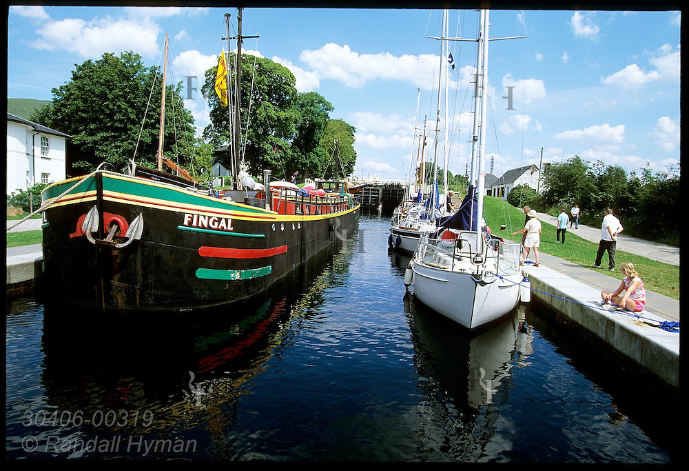 Boats wait for lock to empty as they descend eight-tiered Neptune's Staircase at end of the Caledonian Canal; Ft William, Scotlnd