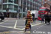 The day after Facebook's Mark Zuckerberg faced Senate Committee questions in Washington, A woman wearing a bold chequered coat crosses New Oxford Street outside the offices of Cambridge Analytica on New Oxford Street, the UK company accused of harvesting the personal details of Facebook users (including Zuckerberg himself) in its data privacy scandal, on 11th April, 2018, in London, England.