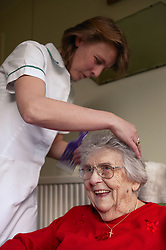 Carer helping an elderly woman with her hair in sheltered accommodation,
